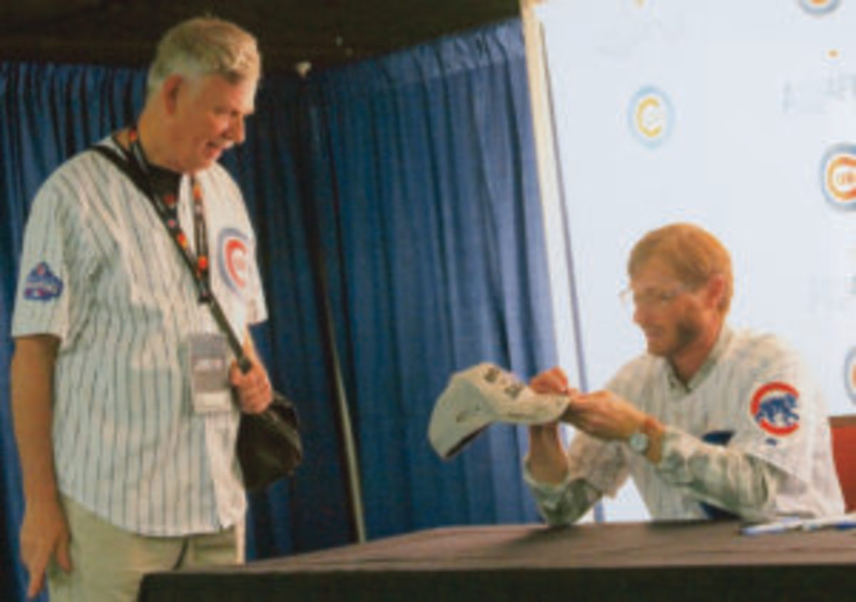 Cubs player Mike Fontenot signs a baseball cap for a fan at one of the autograph stages at the Cubs Convention.