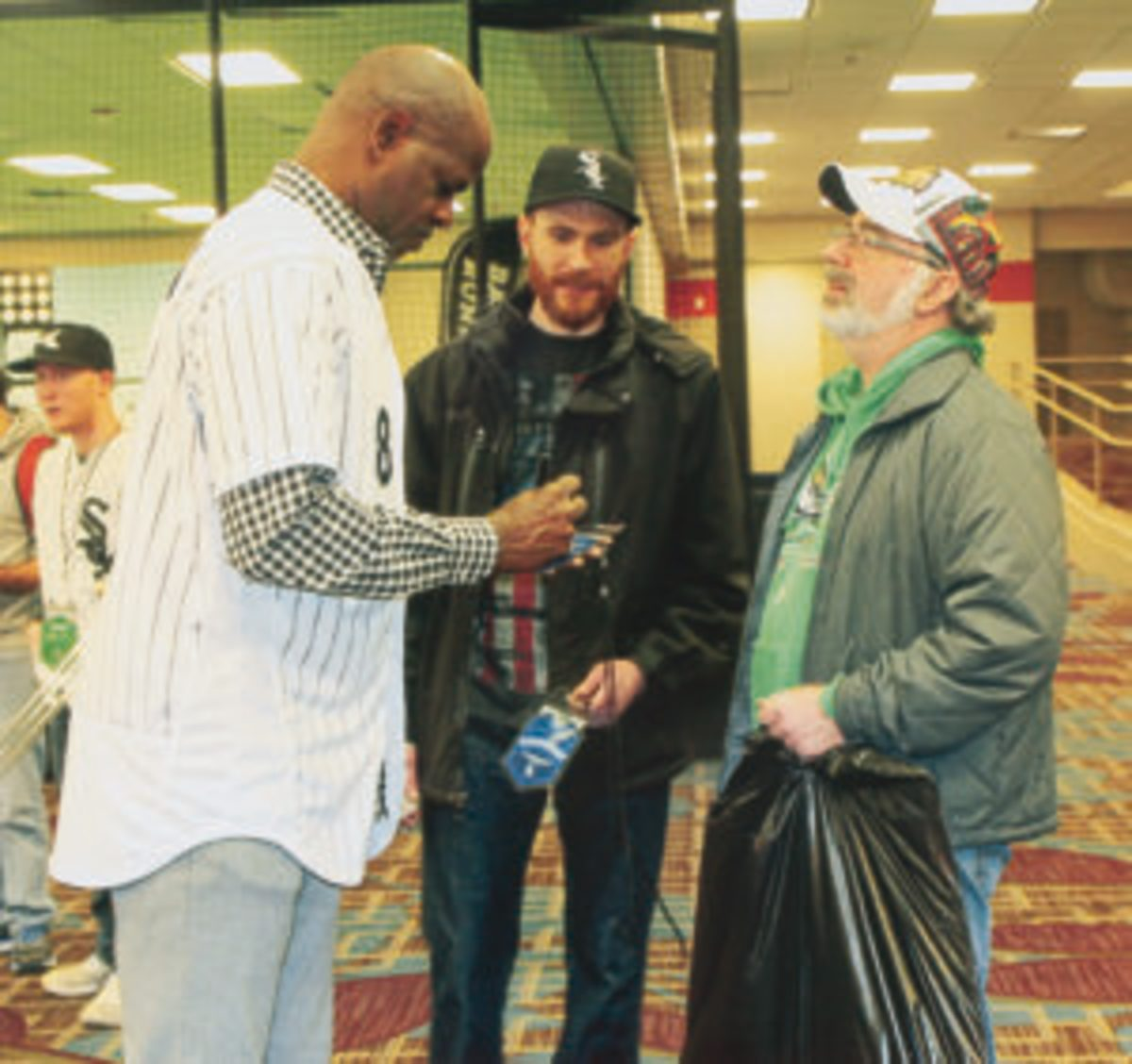 Former Chicago White Sox player and current White Sox coach Daryl Boston signs autographs for fans at Soxfest.