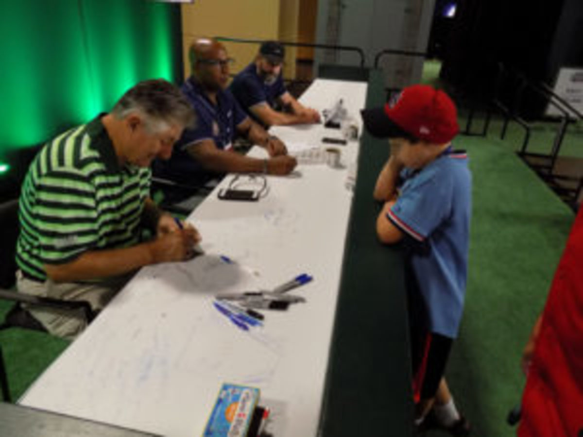Hall of Fame pitcher Rollie Fingers signs an autograph for a young fan.