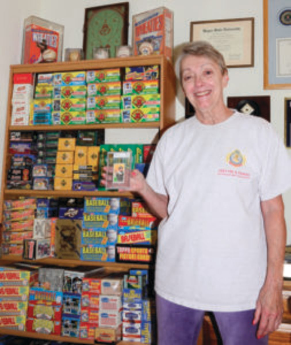 Lea Stoffer-Tatum holds up a T206 Frank Chance card in front of a small portion of her late-husband's sports cards collection. (Photo courtesy Lea Stoffer-Tatum)