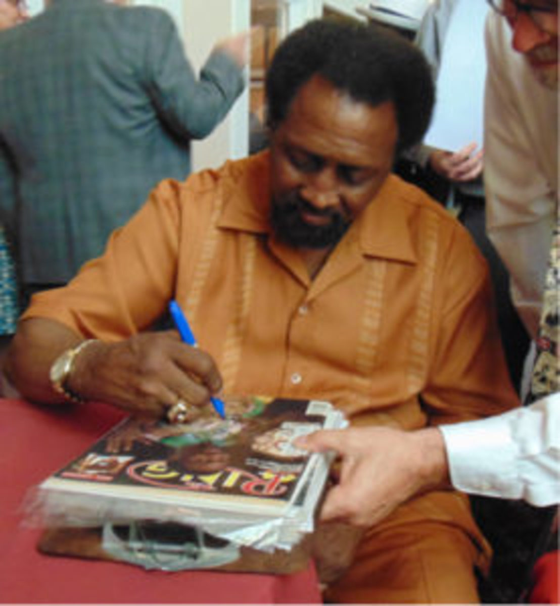 Thomas Hearns signs for a fan at the International Boxing Hall of Fame Cocktail Reception (Robert Kunz photo)