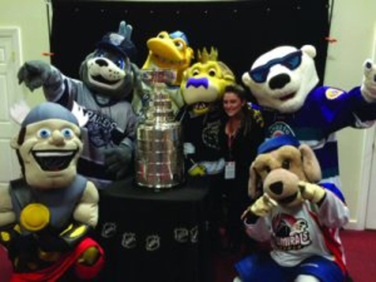Team mascots shown having fun with the Stanley Cup at Fan Fest.