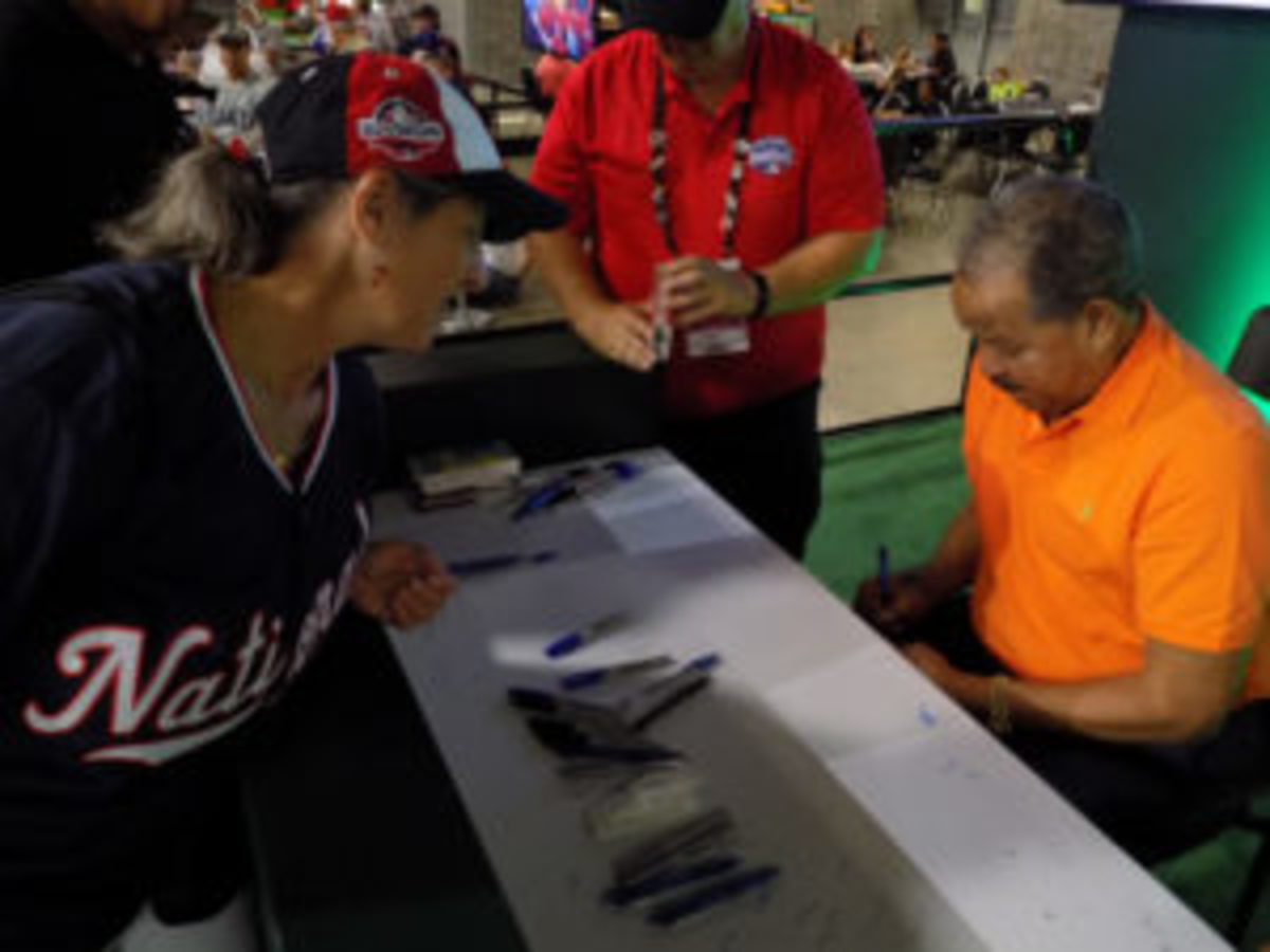 Hall of Fame pitcher Juan Marichal signs an autograph for a fan.