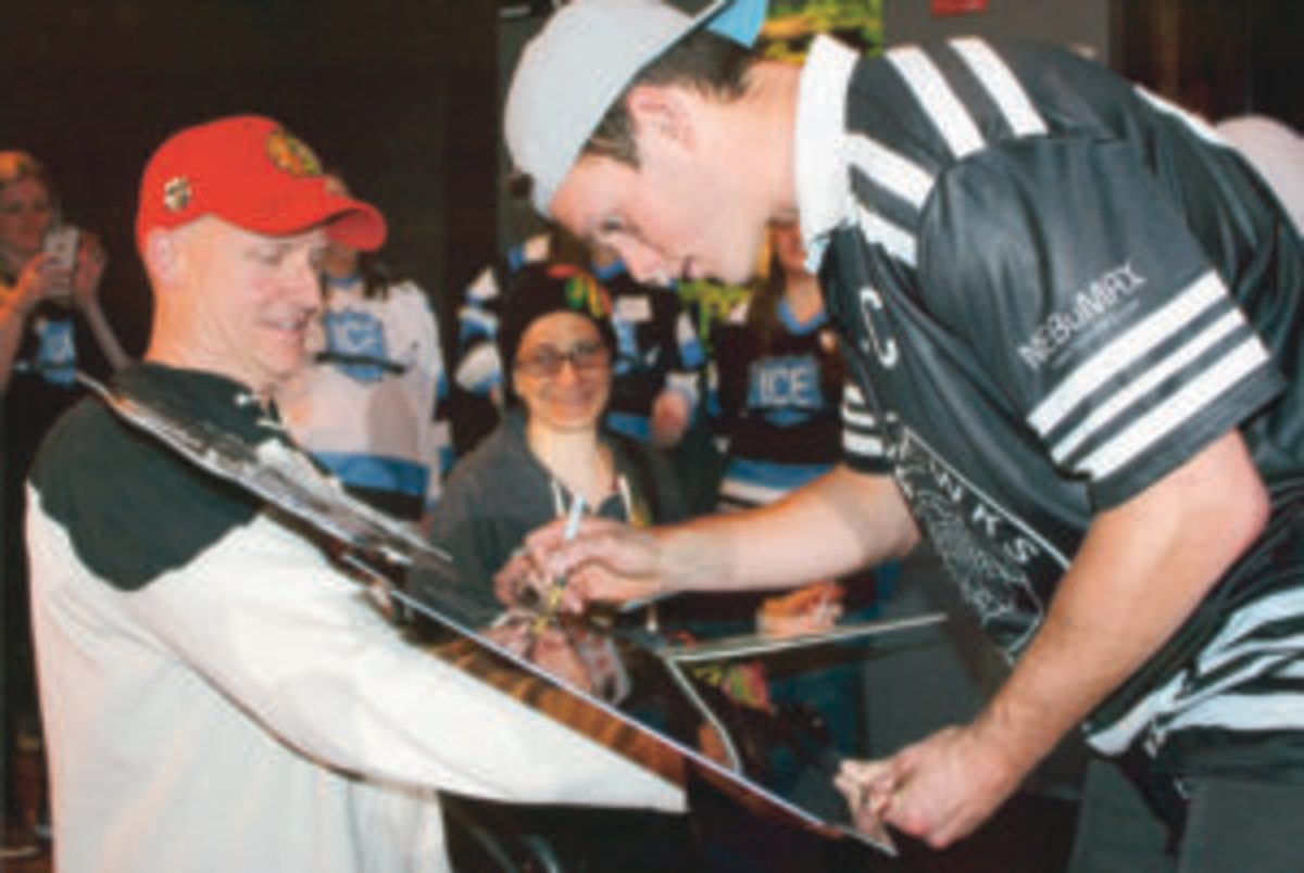 Jonathan Toews signs an item for a fan.