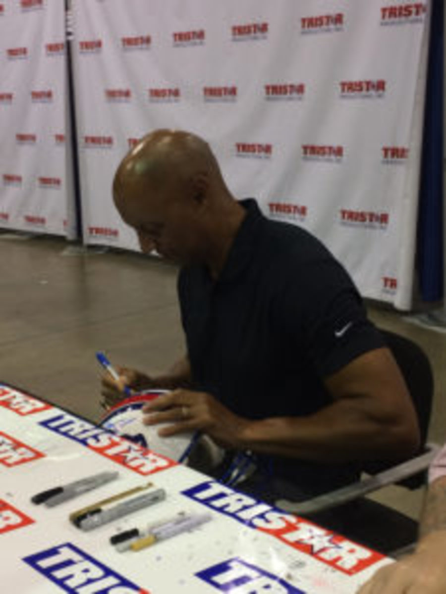 James Lofton signs a helmet for a fan.