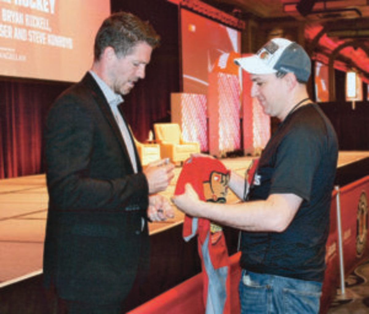 Former Chicago Blackhawks player Colin Fraser (left) signs an autograph for a fan.