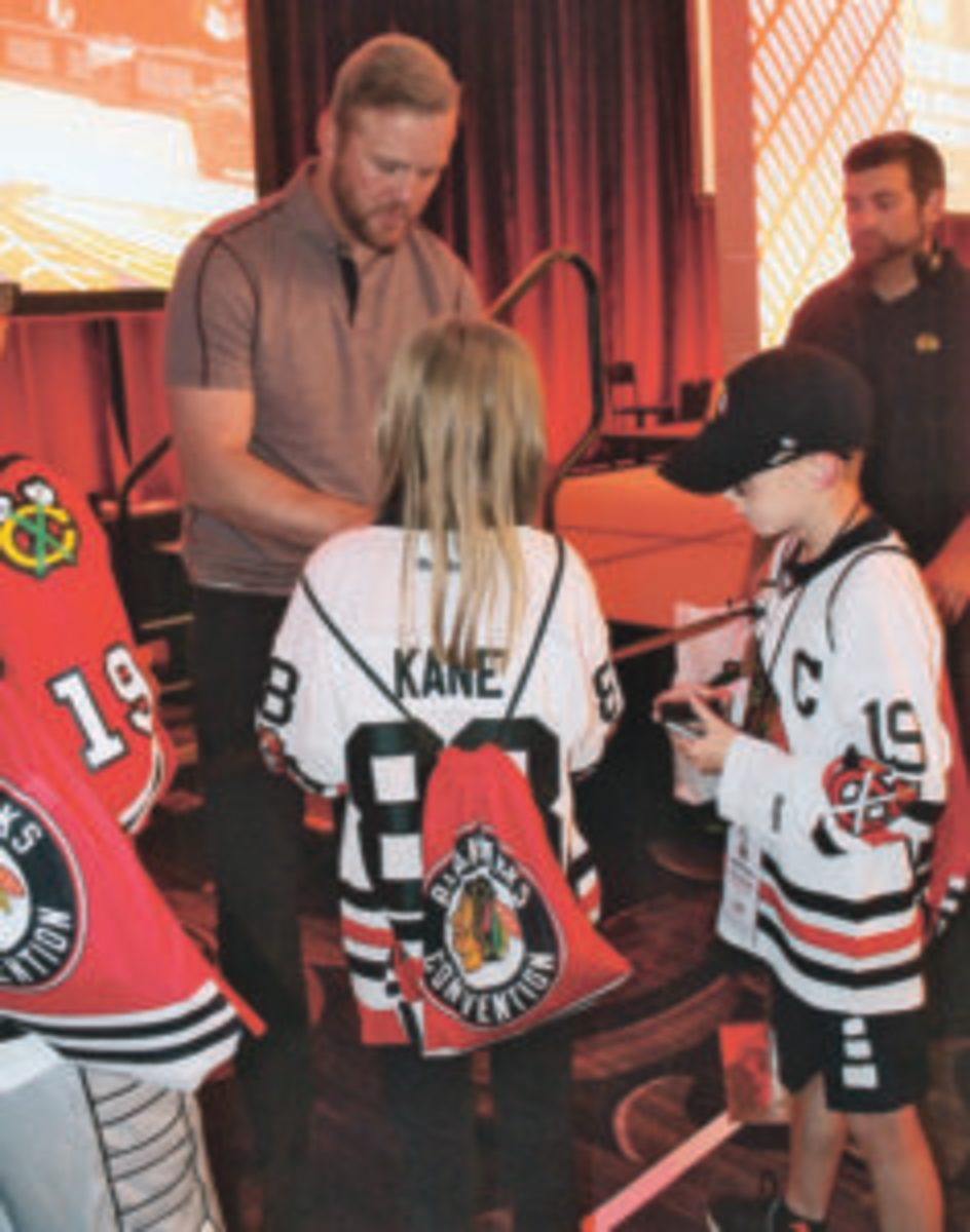 Former Chicago Blackhawks player Bryan Bickell signs autographs for young fans at the Chicago Blackhawks Fan Convention.