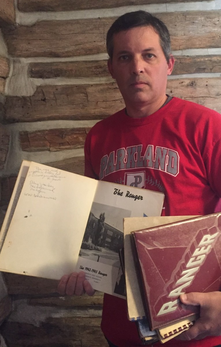 """Jonathan Algard holds up high school yearbooks, including the one with """"Moonlight"""" Graham's signature."""