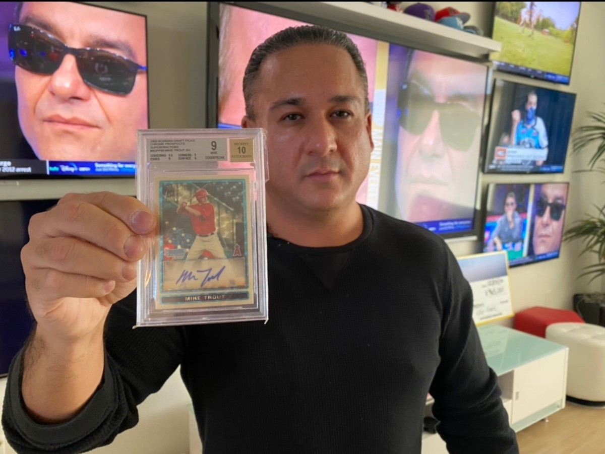 "Dave Oancea, a.k.a. ""Vegas Dave,"" holds up the holy grail of modern-day baseball cards: A 2009 Mike Trout Bowman Draft Chrome Superfractor Autographed."
