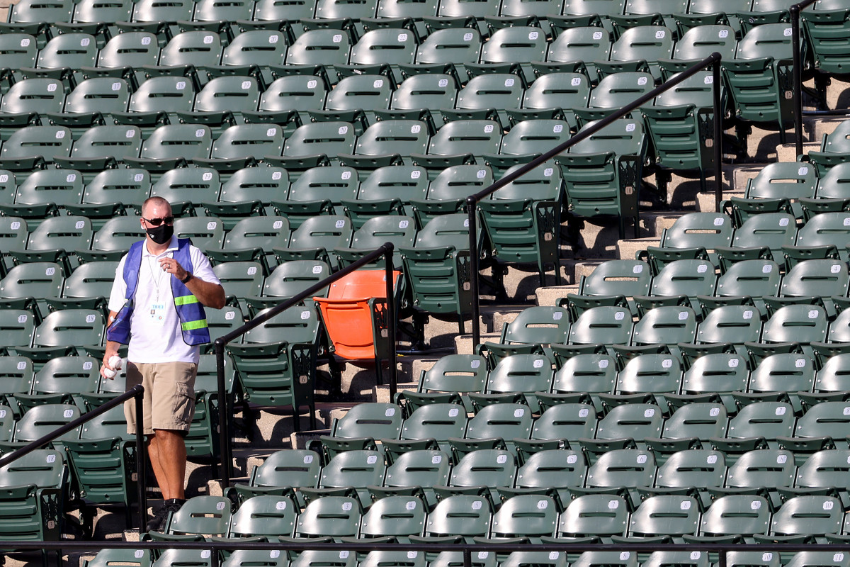 Before the start of the Orioles-Yankees game in Baltimore in July 2020, a member of the MLB Authentication Program removes baseballs hit into the outfield stands during batting practice. Photo: Rob Carr/Getty Images