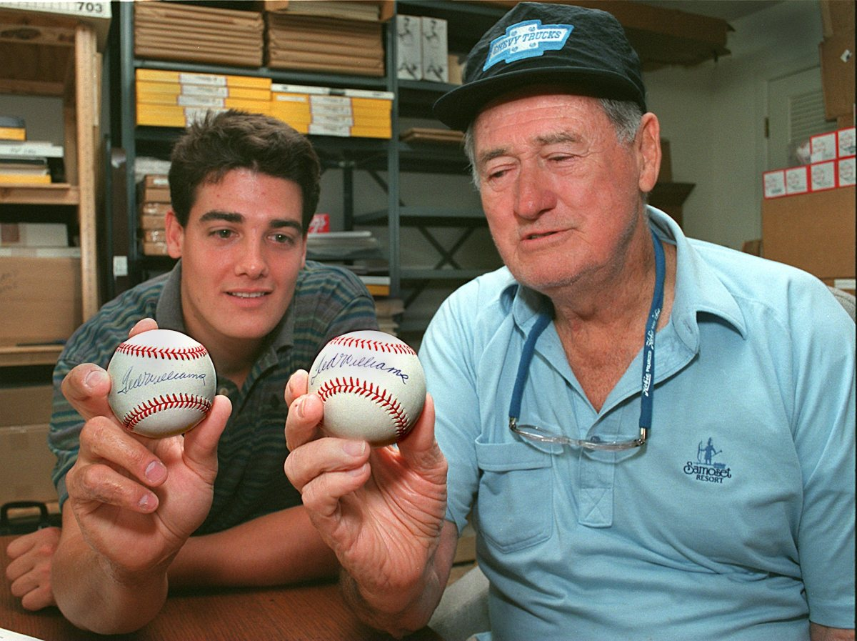 In 1995, Ted Williams holds a baseball he autographed, while his son John Henry holds one that was not signed by Williams. Photo: John Tlumacki/The Boston Globe via Getty Images