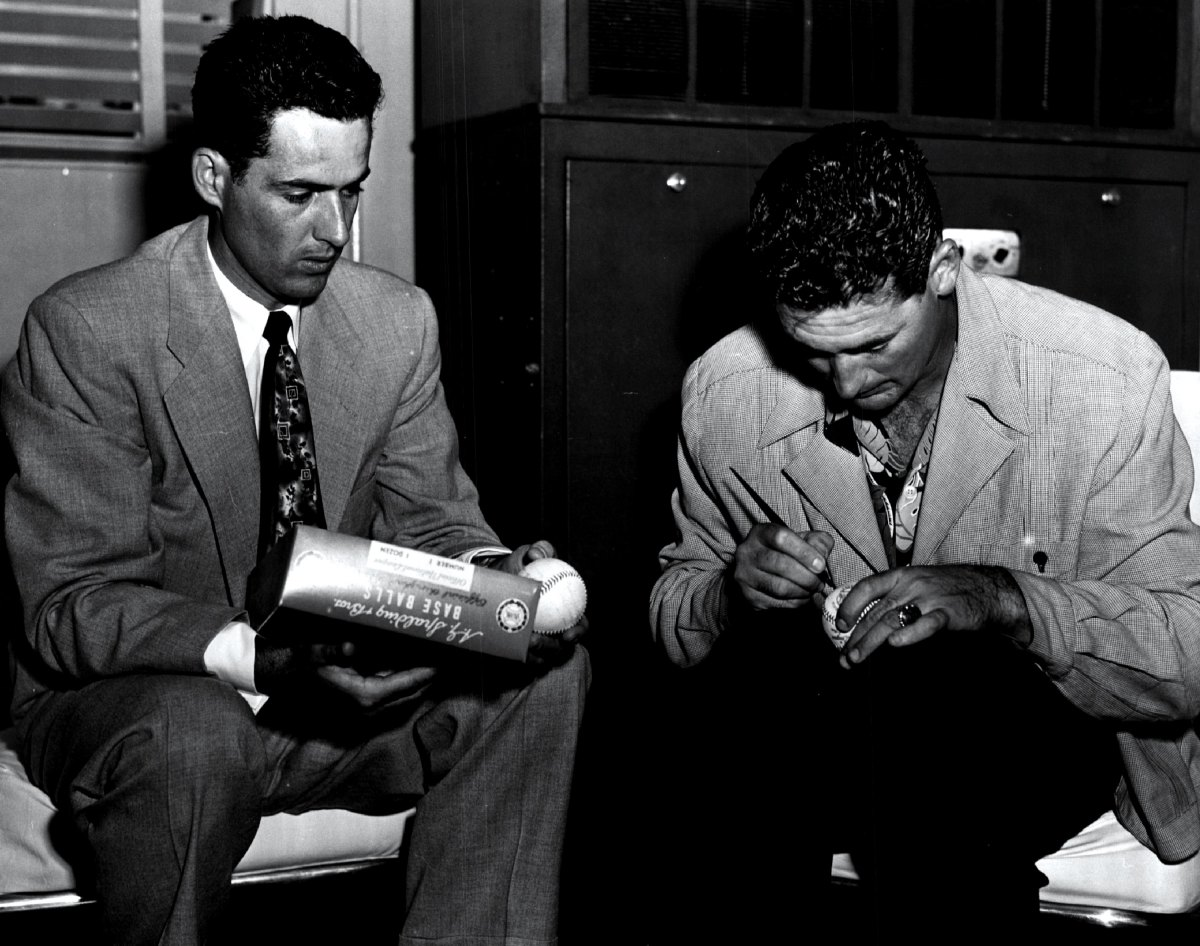 The Splendid Splinter autographs a box of baseballs with the Yankees' Gerry Coleman at a boys baseball training camp in circa 1952. Photo: Sporting News via Getty Images