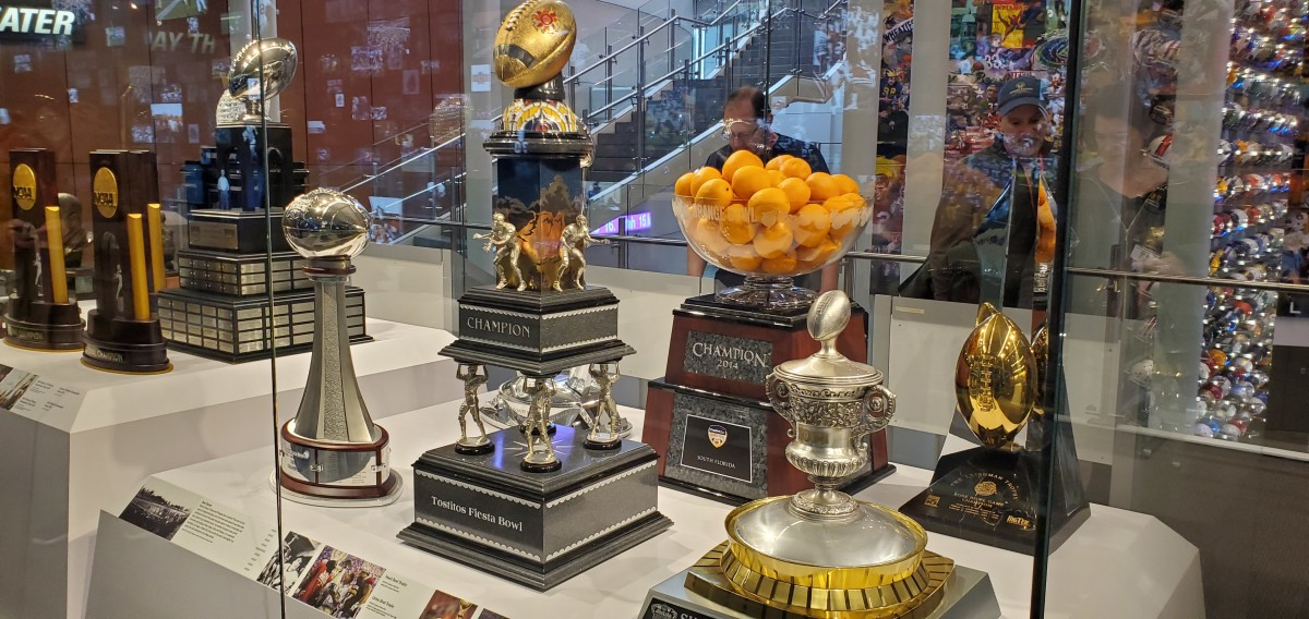 Trophies of major bowl games such as the Tostitos Fiesta Bowl (center) and Orange Bowl.