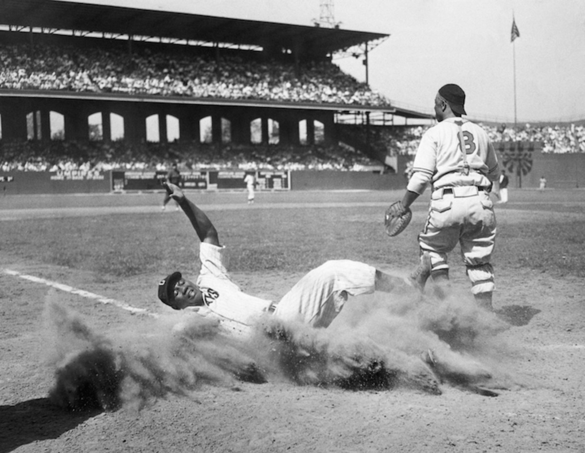 Josh Gibson of the East team creates a cloud of dust as he slides into home after being put out on the play by catcher Ted Radcliffe of the West team in the East-West All-Star Game of the Negro Leagues at Comiskey Park. The West defeated the East, 7-4. Chicago, Illinois, August 13, 1944. Photo: Bettmann/Getty Images