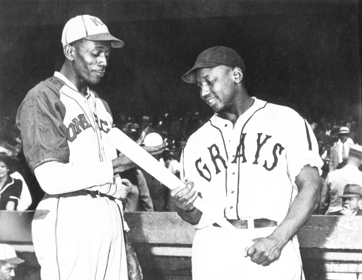 Satchel Paige of the Monarchs talks with Josh Gibson of the Homestead Grays before a game in 1941. Photo: Mark Rucker/Transcendental Graphics, Getty Images