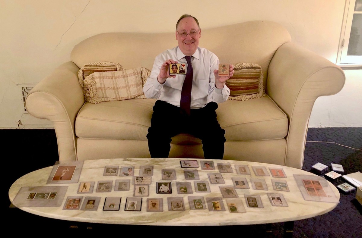 Seymour Stoll holding cards of Sandy Koufax and Hank Greenberg amid his collection.
