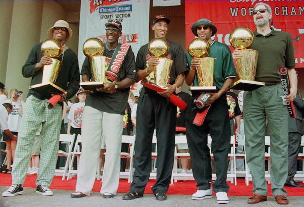 """Key participants of """"The Last Dance"""" hold the five NBA trophies won by the Bulls before their 1997-98 swan song. Photo: Jeff Haynes/AFP/Getty Images"""