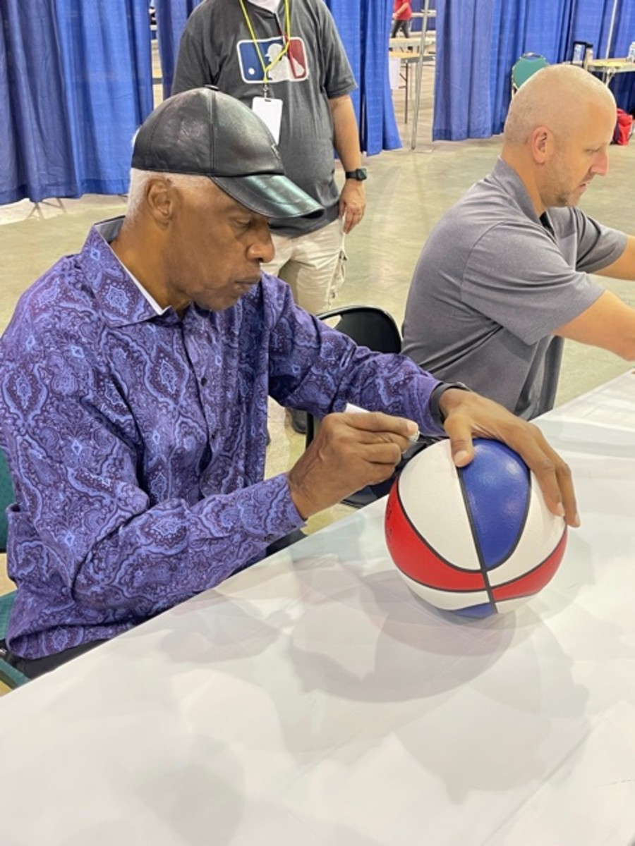 Julius Erving signs one of the iconic ABA basketballs.