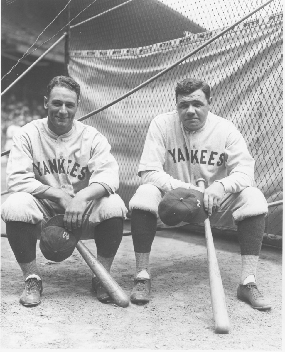 Lou Gehrig and Babe Ruth sit by the batting cage at League Park in Cleveland prior to a game between the Indians and Yankees in July 1927.