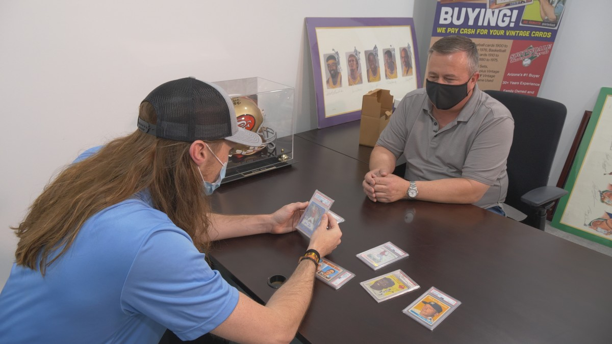 Matt Strahm examines a 2009 Mike Trout auto rookie card with Brian Marcy of Scottsdale Baseball Cards.
