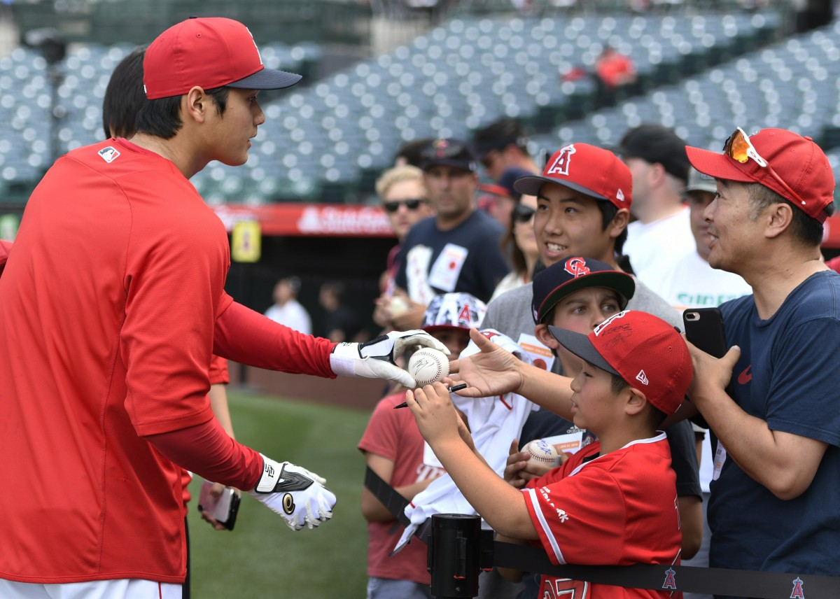 Shohei Ohtani signs autographs for fans at Angel Stadium in 2018.