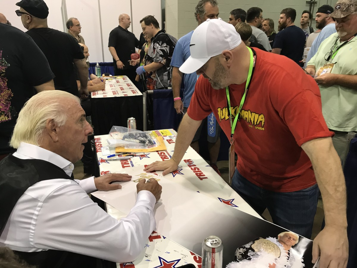 Ric Flair chats with a fan as he signs autographs.