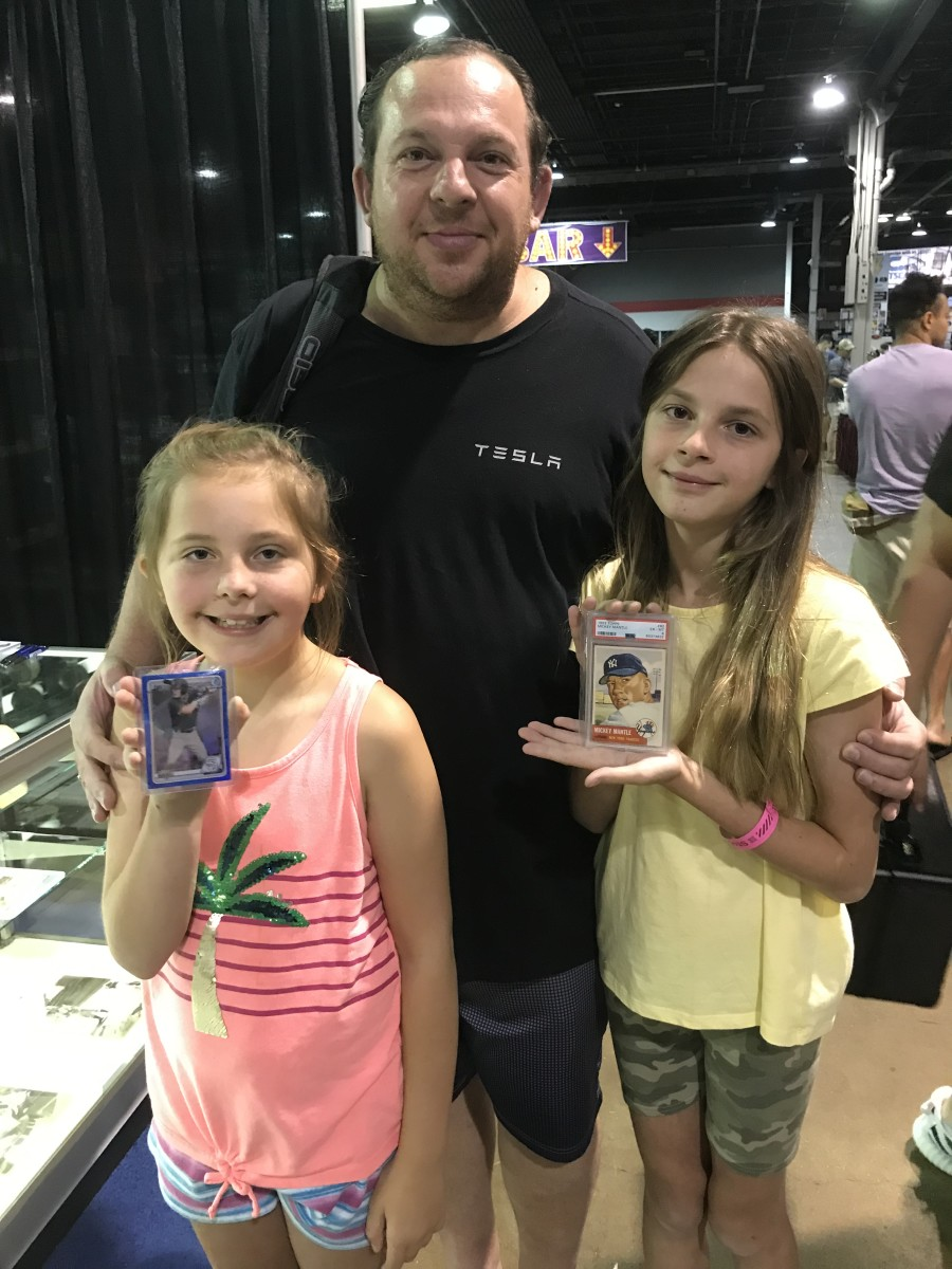 Young collector Karina Alekseev (right) shows off her 1953 Mickey Mantle while at The National with her dad, Victor, and sister, Victoria.