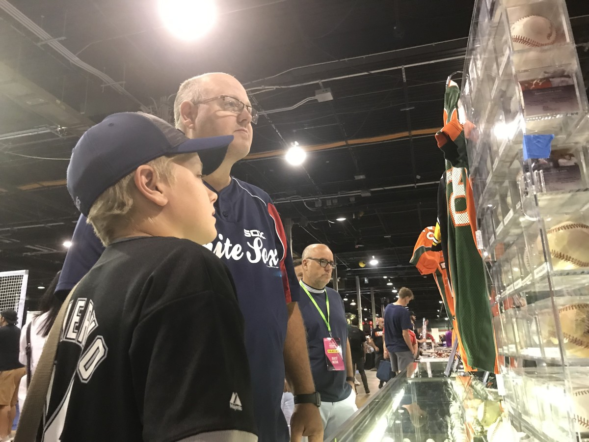 Fitz Suey and his son, Mason, check out some autographed baseballs at The National.