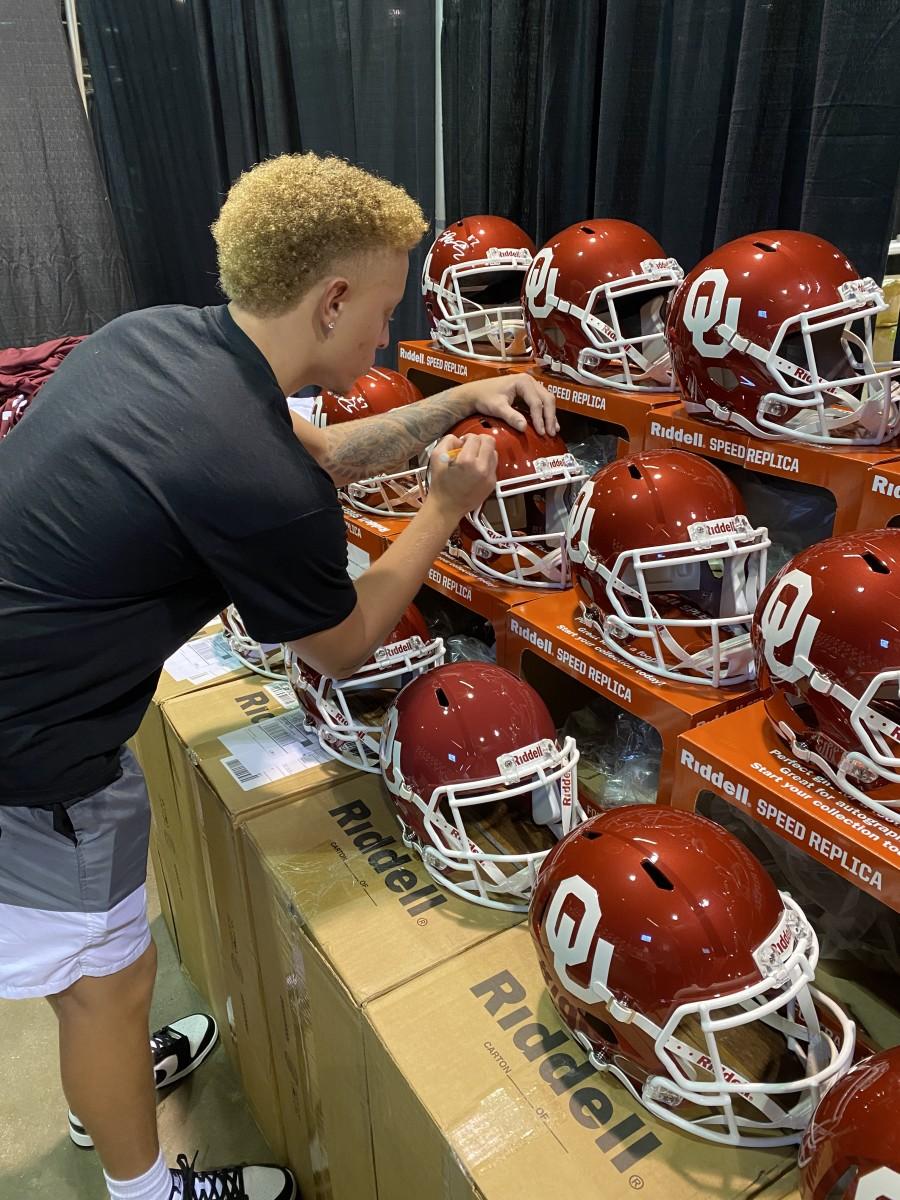 Oklahoma quarterback Spencer Rattler signs helmets.
